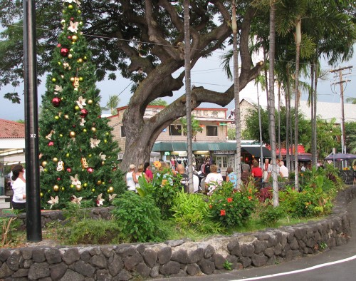 Pedestrians pause to listen to Hibiscus Jam before the holiday tree lights were switched on Friday evening at Emma's Square on Alii Drive.