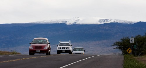 Cars drive down Waikoloa Road with a snow-capped Mauna Kea summit in the background.