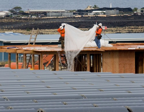 Work crews at Natural Energy Laboratory of Hawaii dump rainwater from a building under construction.
