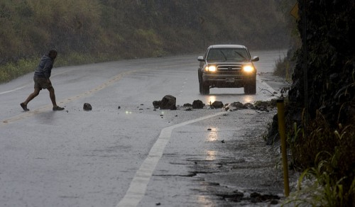 A motorist stops at Laupahoehoe Gulch to clear the Hilo bound lane of a rockslide as heavy rains hit the east side of the Big Island.