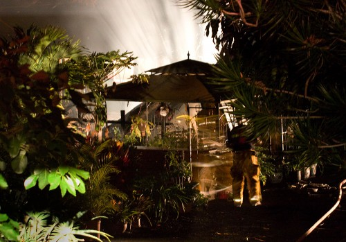 Firefighters hose down the fire scene at Paradise Pottery Studio.