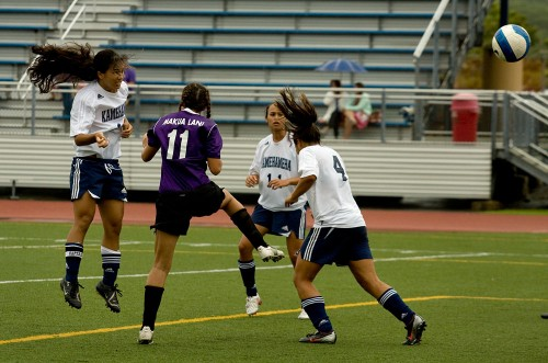 Kamehameha-Hawaii's Pua Hall (15), left, watches her shot sail to the goal for a score in the second half of action against the Makua Lani Lions in Keaau. Kamehameha won the girls match 5-0.