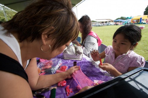 Letty Galoway, left, helps Niann Penaroza, 10 years-old, work on a crafts project creating flowers at the Queen Liliuokalani Children's Center booth during the Family Fun Day at Kurtistown Park.