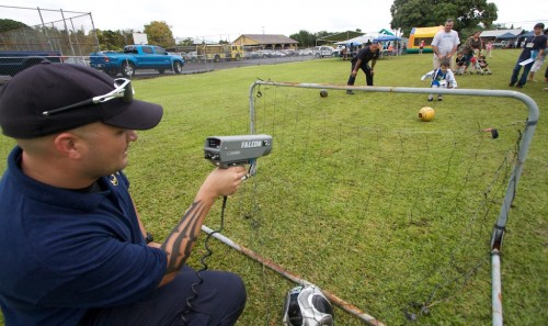 Community Police Officer Jesse Kerr, left, uses a radar gun to check the speed of soccer kicks during the Family Fun Day at Kurtistown Park. The event featured arts, crafts, games, food, sports, entertainment and prizes.