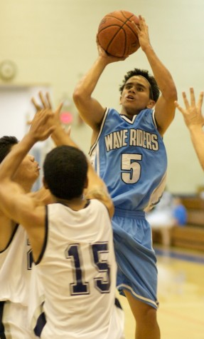 Kealakehe Waverider Jordan Ursua (5) shoots over the Waiakea Warriors Mitchell Shintani (23) and Matthew Libao (15) during boys basketball action at Waiakea.