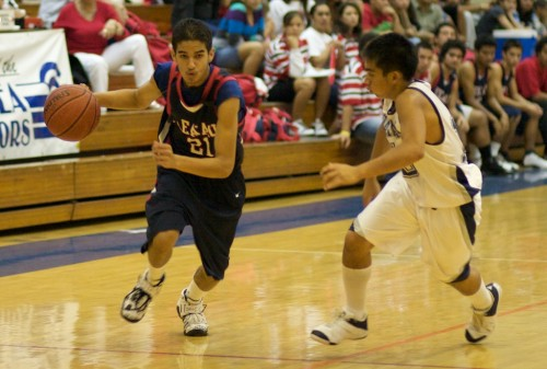 Keaau's Haku Ishibashi (21) drives past Waiakea's Rico Asuncion (10).