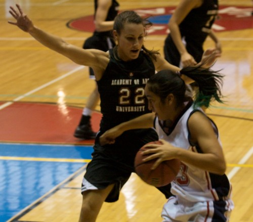 UH-Hilo's Eileen Pineda (23), right, drives past Academy of the Arts player Ali-Tyson Taufoou (22) at Afook-Chinen Civic Auditorium. UH-Hilo leads at the half 47-28.
