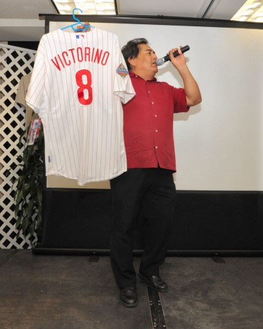 Auctioneer J.E. Orozco holding an autographed Shane Victorino World Series jersey which eventually sold for $700 to a lucky bidder.