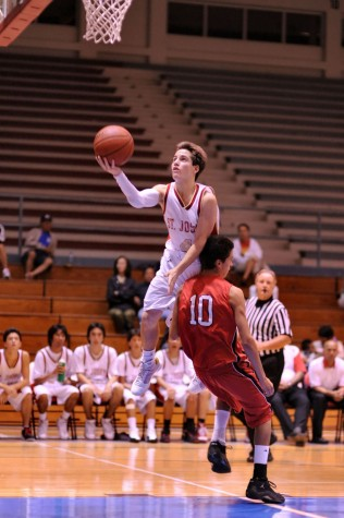 Jacob Andrade of St. Joseph soars to the hoop over Nathan Schenk.