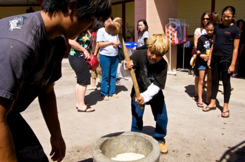 Kelsey Katayama, 11 years-old, works on pounding mochi rice during the mochi tsuki demonstration by Kona Hongwanji Mission.