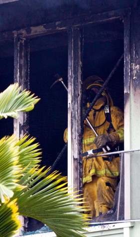 A firefighter takes down loose debris in a home gutted by a fire Wednesday afternoon in Hilo.