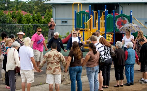 Attendees join hands as the blessing for the new playground equipment in Pahoa is conducted.
