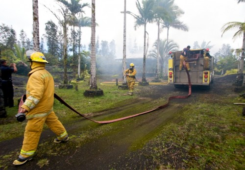 Firefighters lead out hoses to a tanker unit while putting out a structure fire on Ainaloa Drive in Puna.
