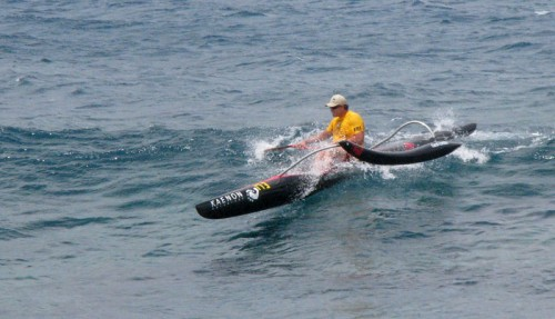 An OC-1 paddler comes in with a flying ama into the finish.