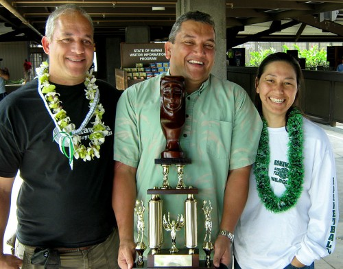 Mayor Billy Kenoi holds the state championship trophy, flanked by assistant coach Donald Awa and head coach Bobbie Awa.