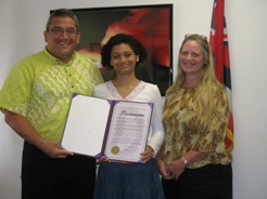 Hawaii Academy of Arts and Sciences student Frances Garry receives a proclamation from Mayor Billy Kenoi as family friend Zoe Avalon looks on.