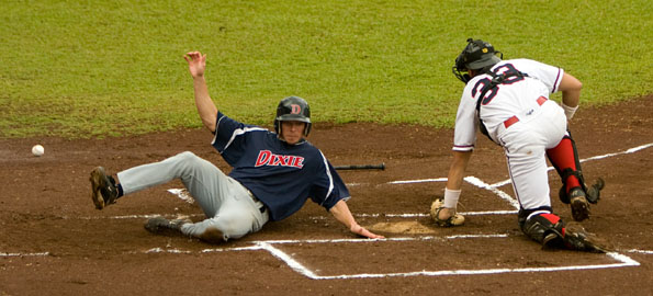 A Dixie State College player slides home safely during the first game of a doubleheader played at Wong Stadium