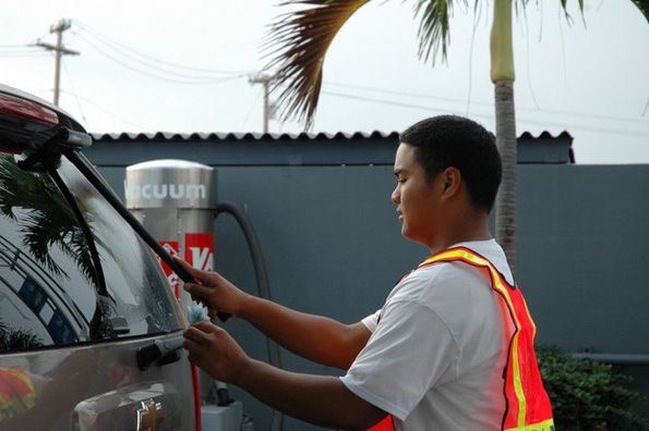 A volunteer puts the shine on a vehicle's window during the car wash. (Photo by KC Strand/courtesy of Special Olympics West Hawaii)