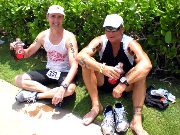 Adam Busek, 47, of Keaau, and Bill Greineisen, 56, of Volcano, relax and enjoy some post-race refreshments. (Hawaii247.com photo by Karin Stanton)