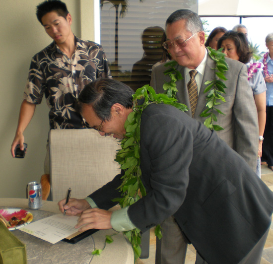 Third Circuit Judge Ronald Ibarra signs the oath as his son-in-law Neal and Chief Justice Ronald Moon look on Monday, May 4 in Keauhou. (Hawaii247.com photo by Karin Stanton)