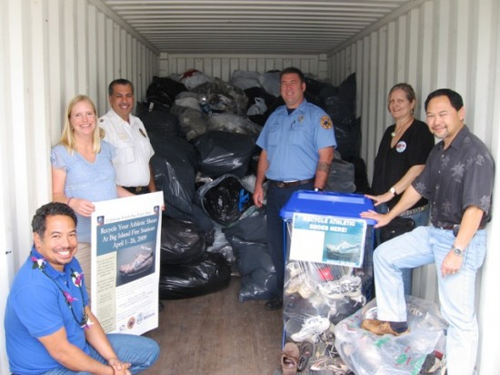 From left, Lono Tyson, Director, Environmental Management, Rebekah Sluss, Environmental Management, Darryl Oliveira, Fire Chief, Rob Wall, Fire Department, Linda Peters, Environmental Management, and Ivan Torigoe, Deputy Director, Environmental Management, help load a container with recycled shoes.