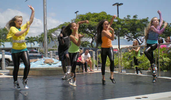West Hawaii Dance Academy hip hop students, including Jeanne Kapela (in orange), show off their latest moves during a recent performance at Kona Coast Shopping Center. (Hawaii247.com photo by Karin Stanton)