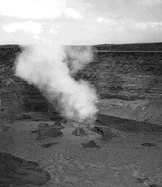 A single low lava fountain emitted a steady stream of gas when photographed by Fred Rackle on July 21, 1952, when Halemaumau Crater was more than twice as deep as it is at present. View is to the southwest. (Photo courtesy of Hawaiian Volcano Observatory)