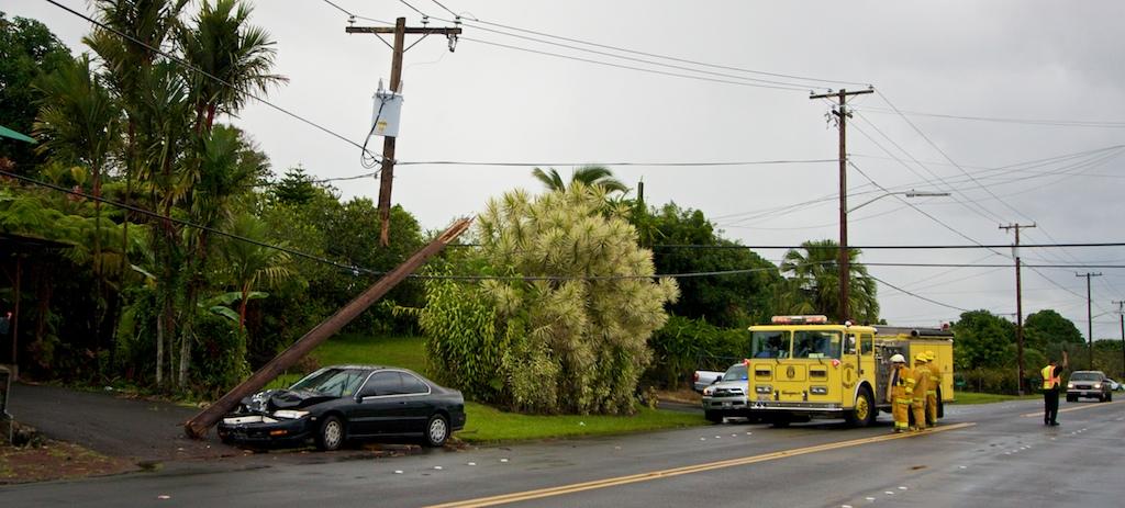 A car in the Puna bound lane of Kilauea Avenue severs a utility pole near E Palai Street.