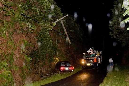 A utility pole dangles from high power lines resting on treetops after being severed by a car. White slotches on the photo are due to rain illuminated by camera flash. Photography by Baron Sekiya/Hawaii247.com