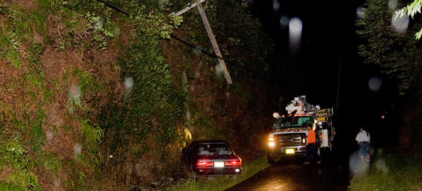 A utility pole dangles over a car which severed it on Ihope Road in Mountain View Tuesday night.