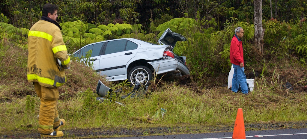 A car in the brush alongside Saddle Road limited traffic to one lane as rescue vehicles occupied the Kona bound lane.