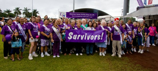 Cancer survivors and caregivers get a group photo after the first lap of the Relay for Life at Victor Wong Stadium in Hilo.