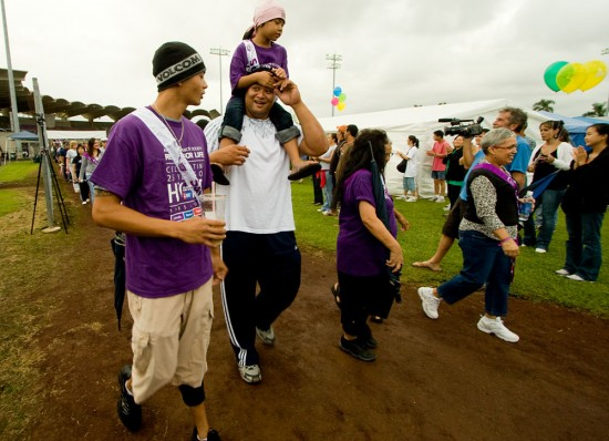 Cancer survivors and caregivers take the first lap around Victor Wong Stadium to open the Relay for Life fundraiser for the American Cancer Society.