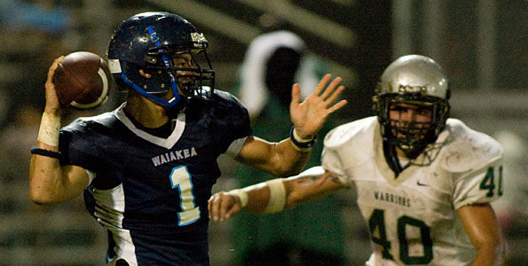 Waiakea quarterback Dylan Bolos (1) back to pass against Kapaa during pre-season football action at a rainy Wong Stadium in Hilo.