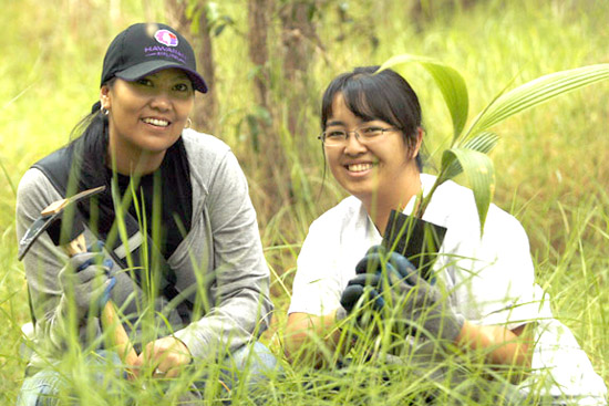 Volunteers Tani-Kaye Sorensen (Human Resources Manager) and Erin Ito (Human Resources Information Systems Manager) of Hawaiian Airlines prepare to plant a loulu palm. (Photo courtesy of Hawaiian Airlines)