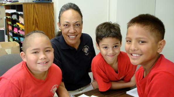 Kauanoe Kamana, 2009 Mellon-Hawaii Doctoral Fellow, with third grade students practicing reading in Hawaiian at Ke Kula O Nawahiokalaniopuu. (Photo courtesy of The Kohala Center)
