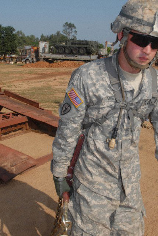 """Spc. Paul West, a mortarman assigned to Troop B, 2nd Squadron, 14th Cavalry Regiment """"Strykehorse,"""" 2nd Stryker Brigade Combat Team, 25th Infantry Division, from Schofield Barracks, Hawaii, removes chains while unloading vehicles in preparation for Exercise Yudh Abhyas 09 in Babina, India. (Hawaii247 photo special by Staff Sgt. Cristina Yazzie)"""