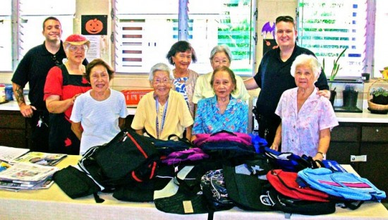 Community Police Officers Scott Amaral, left, and Sandor Finkey pose with volunteers of the Kea'au Nutrition Center, who donated 25 bags to a backpack charity drive.