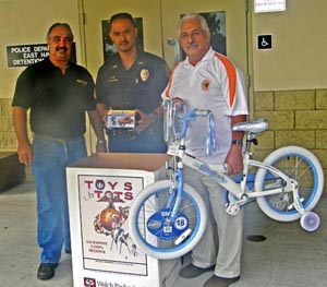 Elsworth Fontes of the Rock & Roll Motorcycle Club, left, poses with Sergeant Regino Saludares and Officer John Stewart (holding bike) at the South Hilo police station, one of eight Police Department donation points for Toys for Tots. (Photo courtesy of the Police Department)