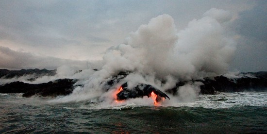 Steam rises from lava flows cascading down the Waikupanaha entry point west of Kalapana.