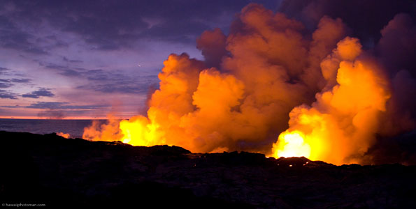 Lava flows into the Pacific Ocean at sunrise in Hawaii Volcanoes National Park.