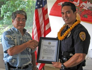 Aloha Exchange Club President Dale Tokuuke presents an 'Officer of the Month' award to Officer Darryl Castillo