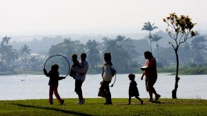 Visitors to Wailoa River State Park walk along the shore as vog blankets Hilo in the background. Kona winds pushed the vog from Kilauea Eastward. Hawaii 24/7 File Photo