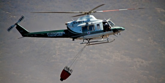 A chartered helicopter comes in to pick-up water near Saddle Road to drop onto the fire on the slopes of Mauna Kea.