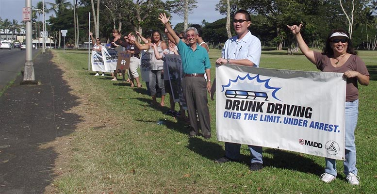 """The Hawai'i  Police Department's Traffic Services Section organized a sign-waving event on Kamehameha Avenue in Hilo on Thursday (August 19) to make motorists aware of the """"Over The Limit – Under Arrest"""" National Crackdown from August 20 to September 6."""