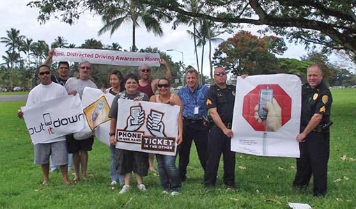 """The Hawai'i Police Department's Traffic Services Section organized a sign-waving event on Kamehameha Avenue in Hilo on Monday (April 4). As the National Highway Traffic Safety Administration has declared April """"National Distracted Driving Awareness Month,"""" this event was to remind motorists about the dangers of the use of electronic devices while driving—especially talking and texting."""