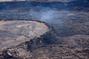 The lava lake'€™s levee stands up to 8 m (26 ft) above the surrounding crater floor. This steep-sided levee impounds the lava and forms what is called a '€œperched'€ lava lake. Pieces of the rim occasionally collapse into the lake, leading to sudden and fast-moving overflows of lava onto the crater floor. Photo courtesy of USGS/HVO