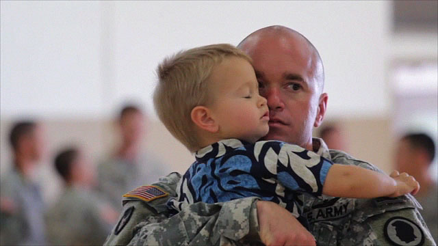 CW2 Peter Bianchi gives his two year-old son Cooper a hug before deployment ceremonies for the Hilo based Hawaii Army National Guard aviation unit. Bianchi's wife Kiara also joined other family members and friends seeing off the troops.