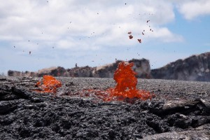 The level of the lava lake on the east side of Pu'u 'O'o crater is even with the craterâ€'s northeast rim. Standing at that spot afforded an eerie view looking across the surface of the lake. A scientist, rescuing equipment, is visible on the crater rim in the background. The view is toward the south. Photos by USGS/HVO