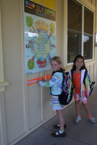 """After biking to school, 1st grader Sadie Blevins places the sticker she earned on the """"Road to a Greener Planet"""" as classmate Nai'a Jones looks on."""